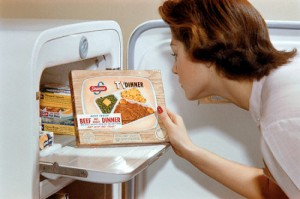 ca. 1950-1965 --- A woman examines a TV dinner box she has taken from the freezer. --- Image by © William Gottlieb/CORBIS